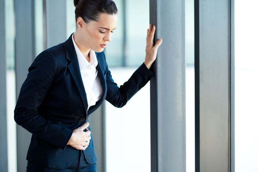 14898895 - young businesswoman having stomach ache in office