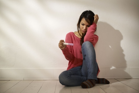 24717006 - women and health, anxious asian girl looking at pregnancy test kit, sitting on ground at home
